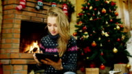 Woman with a tablet near the fireplace video