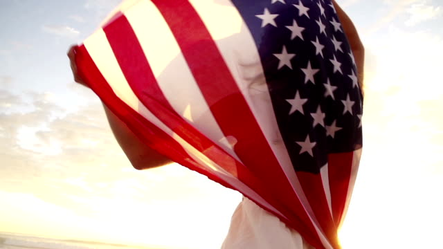 Woman with american flag during sunset in slow motion video