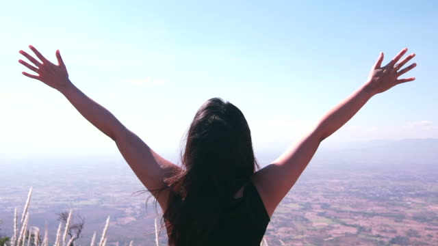 woman with arm raised on top of mountain video