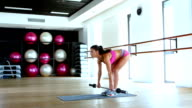 Woman with barbell flexing muscles in gym video
