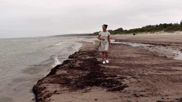 Woman with basket walking along the edge of the sea video