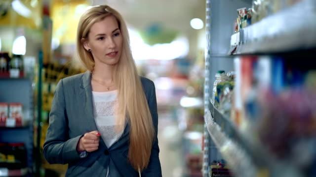 Woman with basket walking in supermarket video