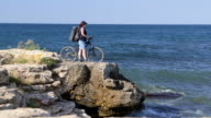 Woman With Bicycle on Rocky Beach video