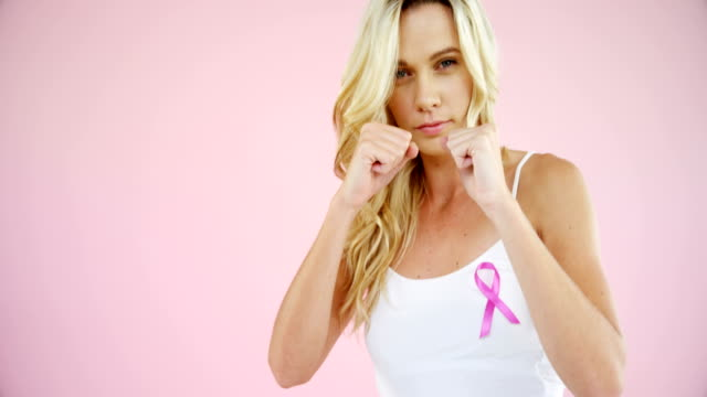 Woman with breast cancer awareness ribbon punching against pink background video