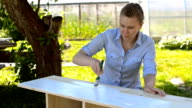 Woman with brush painting wooden furniture. video