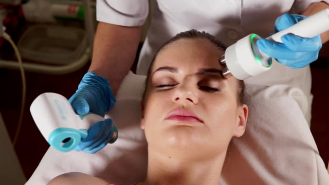 Woman with closed eyes getting rf-lifting in a beauty salon. video