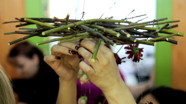 Woman with creative manicure interweaves pieces of metal wire in wooden wreath video