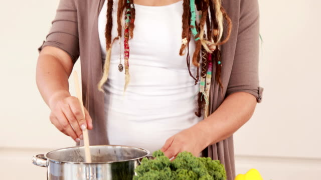 Woman with dreadlocks cooking in the kitchen video