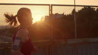 SLO MO TS Woman with earphones running at sunset video