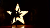 woman with electric guitar. sexy girl in leather, shining star in the background. slow motion, silhouette video
