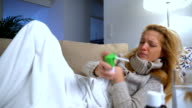 A Woman With Fever Lying On The Sofa, Coughing And Uses Spray For Throat. Dolly video