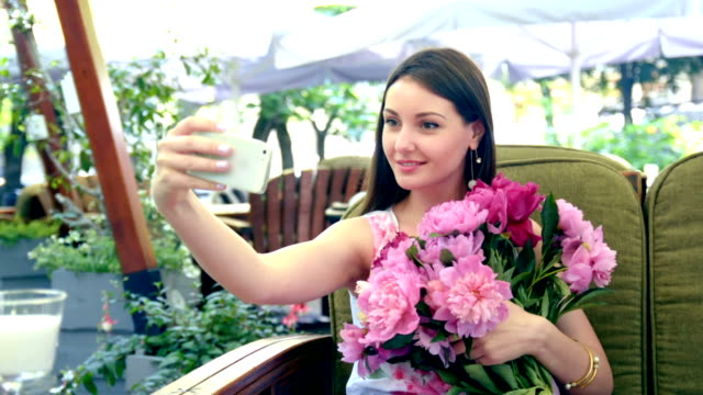 Woman with flowers in cafe making selfie video