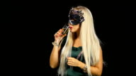 woman with glass of champagne wearing venetian masquerade mask at party, on black video