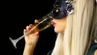 woman with glass of champagne wearing venetian masquerade mask at party, Slow motion video