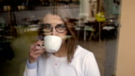 Woman with glasses drinking coffee video