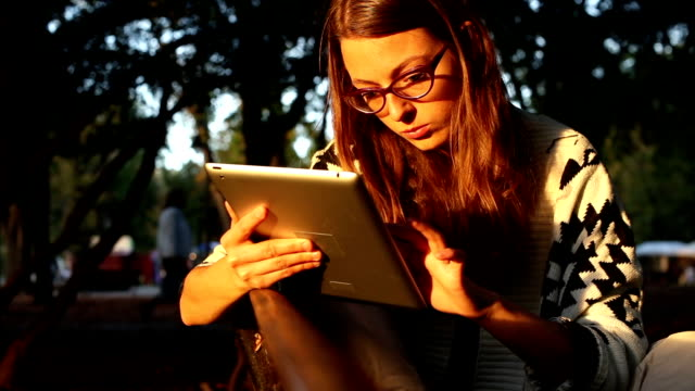 Woman With Glasses In Park Using Tablet video