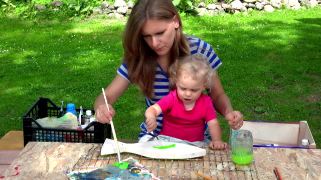 woman with her child daughter paint wooden fish decoration. video