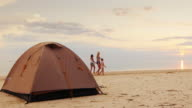 A woman with her two daughters walking along the seashore, in the foreground is a tent for the night video