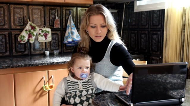 Woman with laptop and baby in a kitchen video
