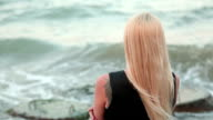woman with long blond hair looking at the sea video