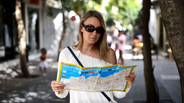 Woman with map in the street. video