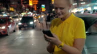 Woman with mobile at the roadside of night Bangkok, Thailand video