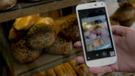 Woman with mobile taking shot of bread in the bakery video