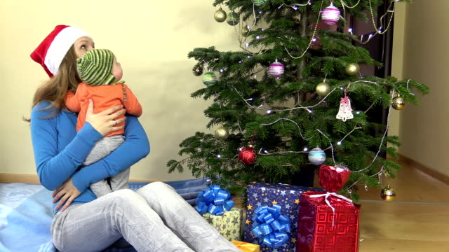 woman with newborn baby look at decorated Christmas fir tree video