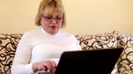 Woman with notebook. Senior woman types text using laptop video