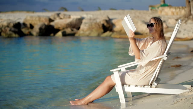 Woman with pad making photos of sea sitting in the deck chair on beach video