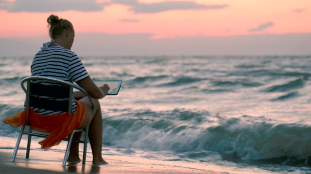 Woman with pad sitting on chair by rough sea video