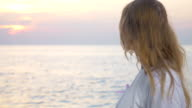 Woman with pink awareness ribbon by the sea video