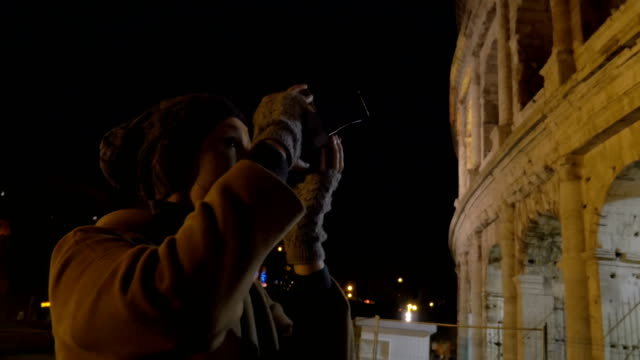 Woman with retro camera shooting Coliseum at night video