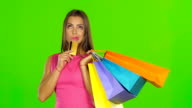 Woman with shopping bags and credit card. Green screen. Close up video