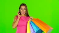 Woman with shopping bags talking on the phone. Green screen Close up video