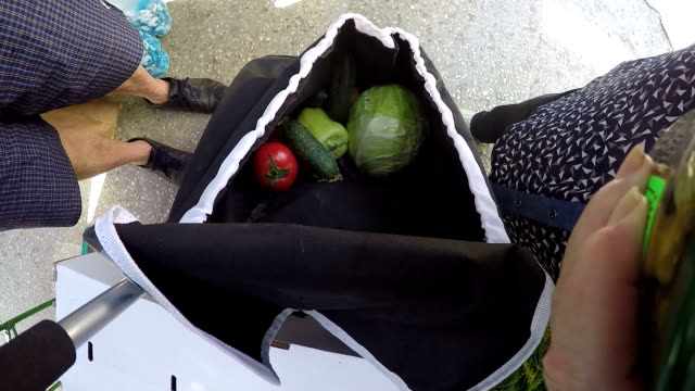 Woman with shopping grocery bag buying fresh produce at local farmers market video