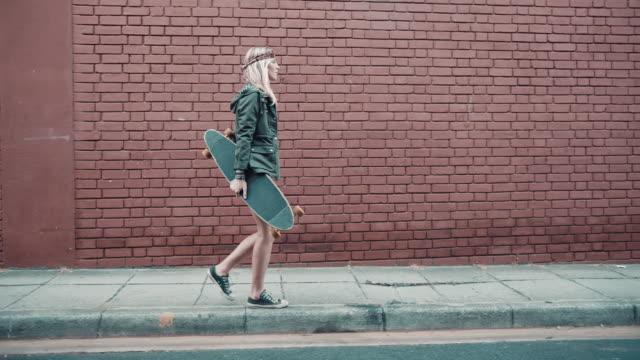 Woman with skateboard walking on street video