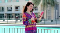 Woman with smartphone stands near blue pool and talks through skype video