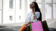 Woman with smartphones and shopping bags walking video