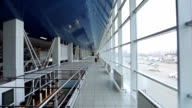 Woman with suitcase, talking on phone on second floor of airport video