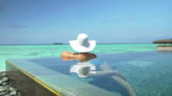 Woman with sun hat relaxing in ocean pool in Maldives video