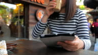 Woman with tablet computer in cafe video