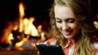 Woman with tablet near the fireplace video