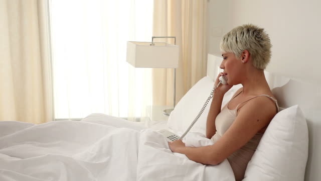 Woman with telephone in bedroom video