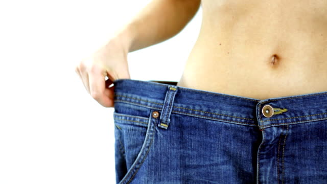 Woman with too big jeans showing weight loss video