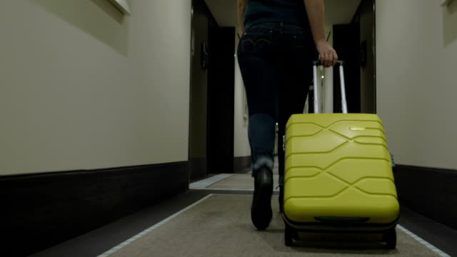 Woman with trolley bag looking for room in hotel video