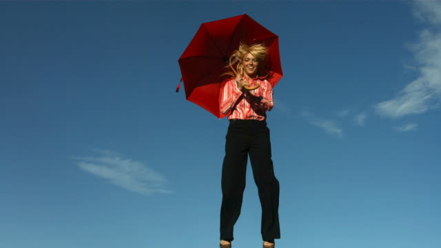 Woman with umbrella jumps into air, slow motion video