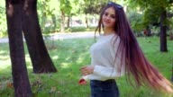 Woman with very long hair whirls and turns around in slow motion video