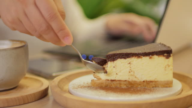Woman working at home with laptop and coffee , cutting chocolate cake video