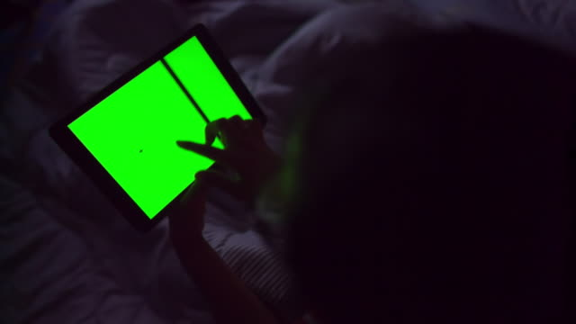 Woman working at night in front of green screen video